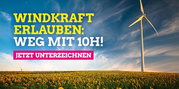 """Ein Windrad steht inmitten eines Sonnenblumenfeldes, die Szene ist in Abendlicht getaucht. Auf dem Bild der Text: """"Windkraft erlauben: Weg mit 10H! Jetzt unterzeichnen"""""""