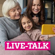 """Drei Generationen schauen zusammen auf ein Handy: Eine Großmutter, eine Mutter und eine Tochter im Grundschulalter. Dazu der Text """"Live-Talk"""""""