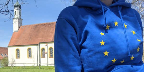 Im Vordergrund ist ein blauer Pulli mit den Europasternen drauf zu sehen, im Hintergrund eine kleine Kirche in der bayerischen Landschaft