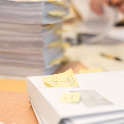 Viele Stapel Papier auf einem Schreibtisch, einige mit Post-Its versehen