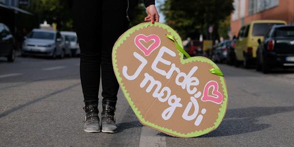"""Nahaufnahme des Demoschilds einer jungen Frau: Das Schild hat die Form eines Lebkuchenherzens, drauf steht """"Erde, I mog di"""""""
