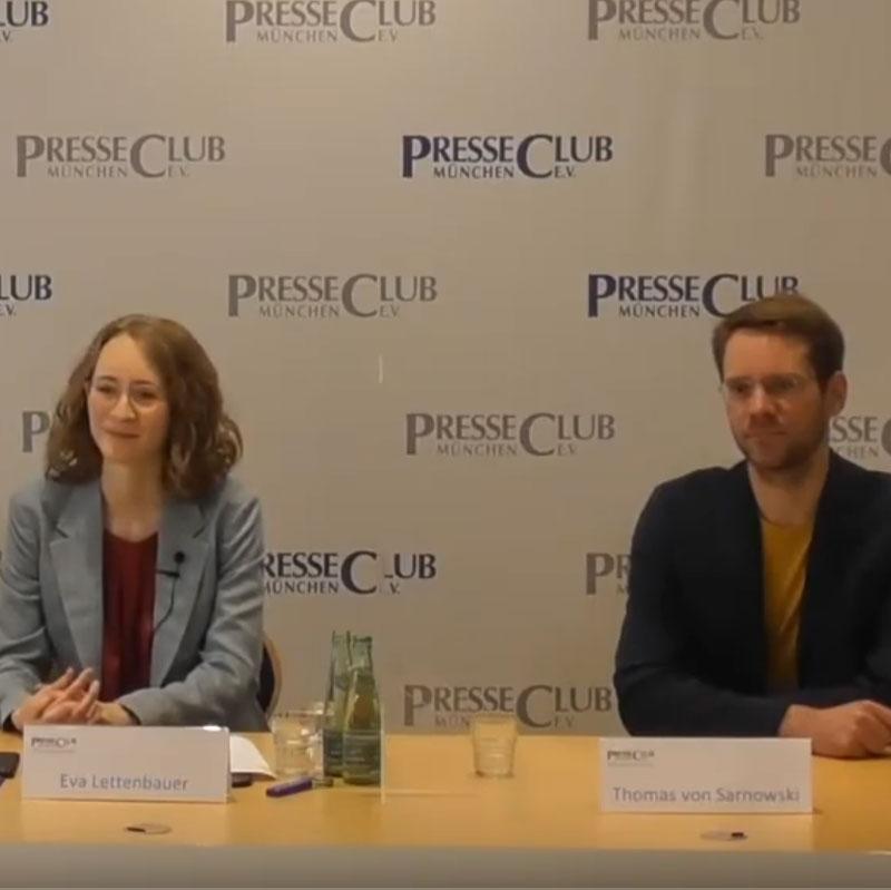 Eva Lettenbauer und Thomas von Sarnowski sitzen an einem Tisch vor einer Wand, auf der das Logo des Presseclubs abgebildet ist