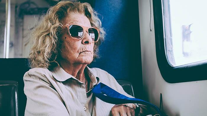 Bild: Eine Frau mit Sonnenbrille sieht aus dem Busfenster