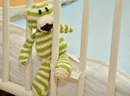 teddybär schaut durch Gitter eines leeren Kinderbetts