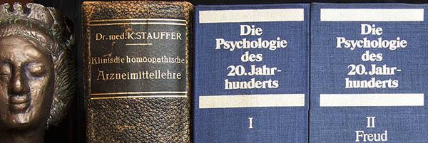 Büste neben antiken Homöopathie- und Psychologiebüchern
