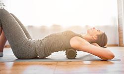Eine junge Frau liegt auf einer Sportmatte auf dem Boden und hat die Beine angewinkelt. Sie rollt ihren Rücken über eine Rückenrolle und stützt mit ihren Händen den Kopf ab.