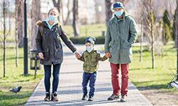 Familienspaziergang zu Coronazeiten: Eine junge Frau und ein junger Mann halten in ihrer Mitte einen kleinen Jungen an den Händen und laufen auf einem gepflasterten Weg durch einen Park. Alle drei tragen eine Maske und blicken in die Kamera.