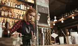 Eine Frau im karierten Hemd steht hinter einer Baar und mixt Cocktails. Sie hat einen kleinen Haardutt und trägt eine Schürze. Im Hintergrund sind verschwommen Getränkeflaschen, Gläser und Lichte zu erkennen.