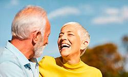 Eine ältere Frau mit kurzen Haaren und in Rollkragenpulli und ein älterer Mann mit Hemd umarmen sich. Der Mann ist eher von hinten zu erkennen; die Frau lächelt über das ganze Gesicht. Im Hintergrund befinden sich Bäume, die verschwommen sind.