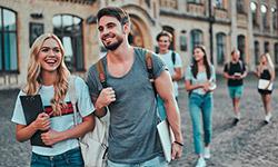 Eine junge Frau und ein junger Mann laufen einer Gruppe voran auf einem Hof vor einem großen Gebäude entlang. Sie tragen Rucksäcke auf den Schultern und Unterlagen in den Händen. Beide lächeln und sehen zufrieden aus. Die restlichen Personen im Hintergrund sind verschwommen.