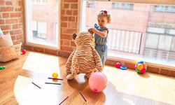 Ein kleines Kind steht im Kindergarten vor einem großen Fenster. Sie hält einen großen Stoffbären am Ohr. Um sie herum liegen Stifte, Luftballons und weitere Spielsachen.