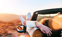 Eine Frau sitzt in einem Cabrio und hängt ihre Füße über die Autotür nach draußen. Mit ihren Händen hält sie sich am Sitz fest. Im Hintergrund sind verschwommen Berge und ein Sonnenuntergang zu erkennen.