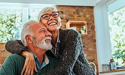Ein älterer Mann sitzt am Küchentisch, eine ältere Frau mit Brille steht hinter ihm und hat ihre Arme um seine Schultern gelegt. Sie freuen sich und lächeln. Im Hintergrund befinden sich eine Küchenzeile und ein Fenster, durch das Bäume zu erkennen sind.