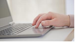 Eine männliche Hand liegt auf einen silbergrauen Laptop, der auf einem weißen Schreibtisch steht.