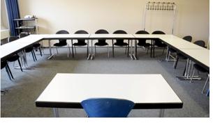 Aufnahme eines leeren Seminarraumes aufgenommen vom Tisch des Dozenten. An der rückwärtigen Wand steht eine Garderobe und ein Tisch mit einem Beamer.