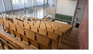 Blick von oben, aus den Sitzreihen, auf einen leeren Vorlesungssaal