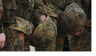 Mehrere Soldaten stehen in einer Reihe und halten ihre Helme in der Hand.
