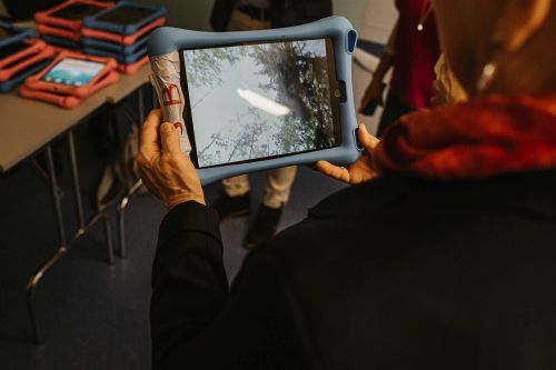 Frau hält blaues Computer-Tablet in der Hand.
