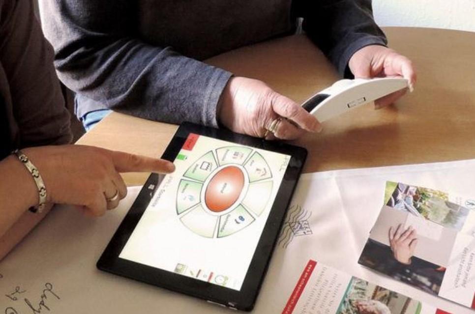 2 Personen sitzen am Tisch blicken auf ein Tablet und ein Warnsystem.