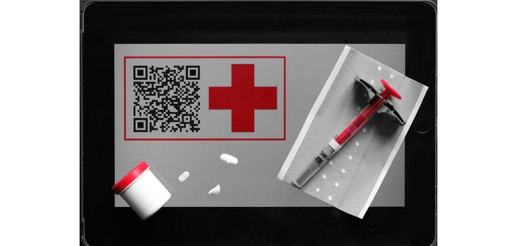 Ein DRK Tablet mit Logo, QR-Code. Darauf liegen einige Tabletten, eine Spritze und ein Pflaster.