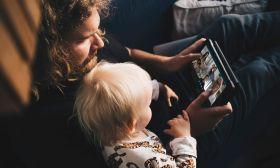 Eine Mutter sitzt mit Kind auf einem Sofa. Beide schauen in ein Computer-Tablet.