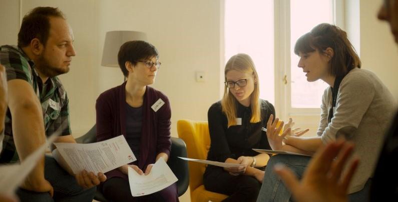 Vier Personen sitzen für eine Gruppenarbeit im Kreis zusammen.