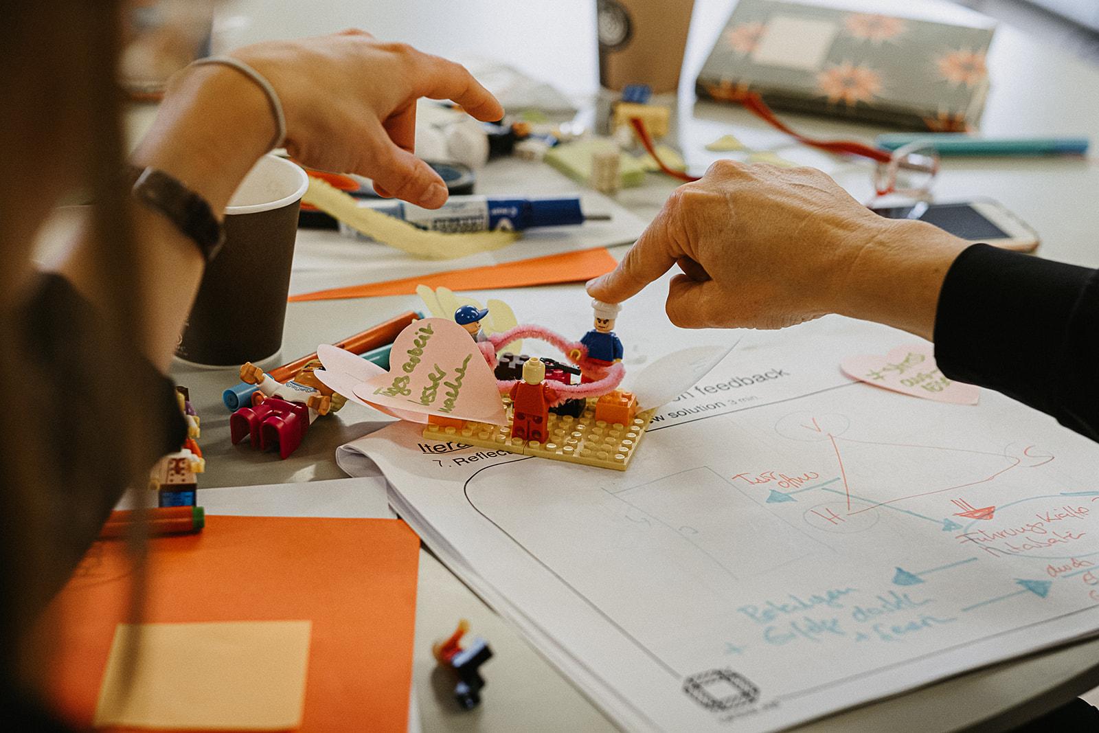 Auf einem Tisch liegen verstreut Papiere. In der Mitte ist ein Lego-Bausatz, auf den ein Zeigfinger einer Hand zeigt.