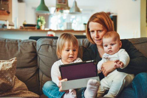 Frau sitzt mit 2 Kleinkindern auf der Couch, sie schauen gemeinsam auf ein Tablet.