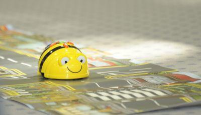 Eine Roboter-Biene fährt über einen Teppich mit Straßenführung.