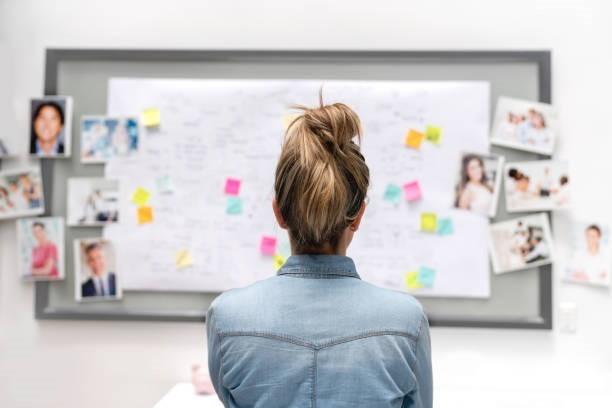 Frau steht vor Whiteboard mit diversen Notizen dran und denkt nach.