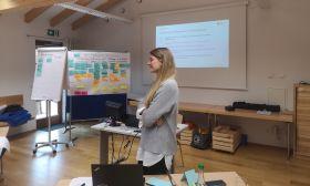 Bettina Stuffer steht im Workshopraum in der Mitte.
