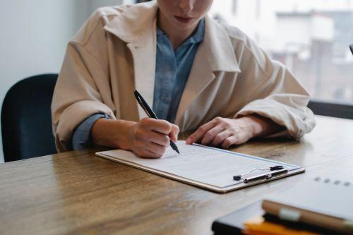 Person füllt Formular am Klemmbrett am Tisch aus.