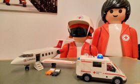 DRK-Playmobil-Figuren mit VR-Billen auf stehen vor DRK-Krankenwagen und Flugzeug
