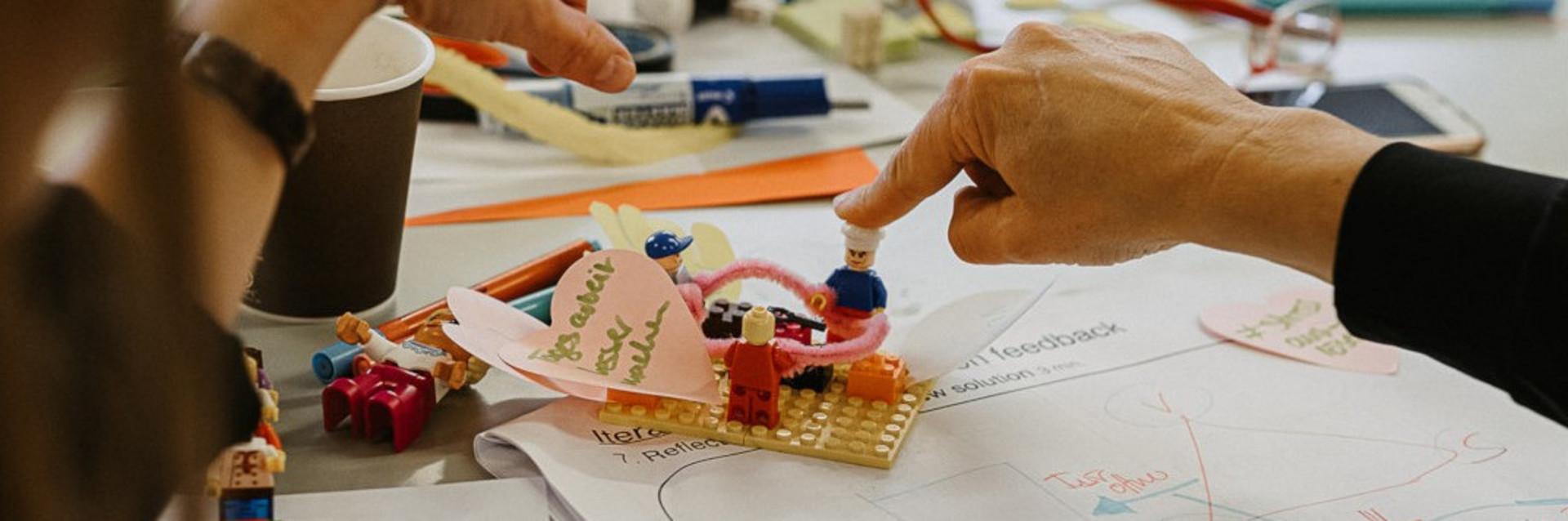 Legobausteine und Hände als Symbolbild für das Bauen von Prototypen