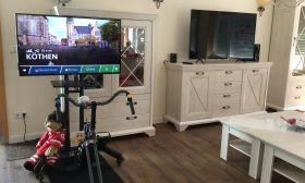 Indoor-Fahrrad mit Flachbildschirm für eine virtuelle Fahrradtour durch Köthen und Mobiliar in einer Seniorenresidenz