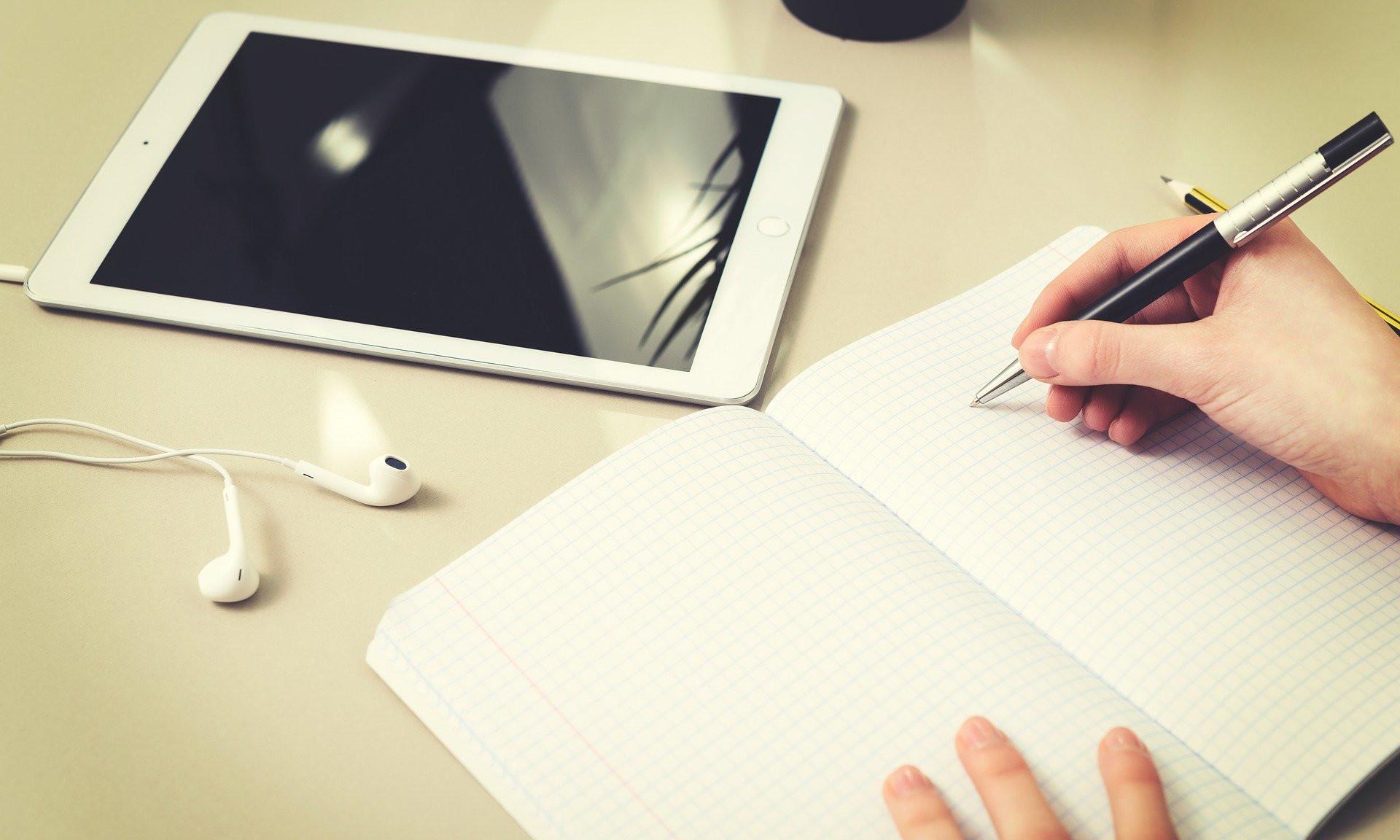 Auf dem Tisch liegt ein Tablet, davor schreibt eine Person in Notizbuch.