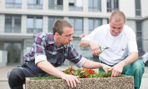 Zwei Menschen machen Gartenarbeit an einem Beet vor einem Gebäude.