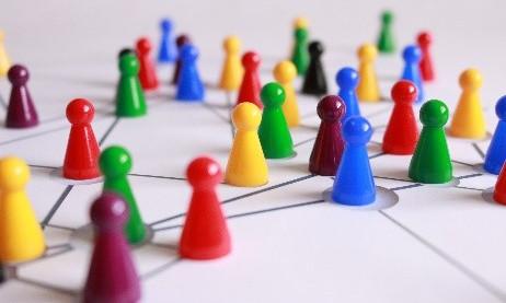 Mensch-Ärger-Dich-Nicht Spielsteine stehe auf einem Tisch und sind mit Linien verbunden