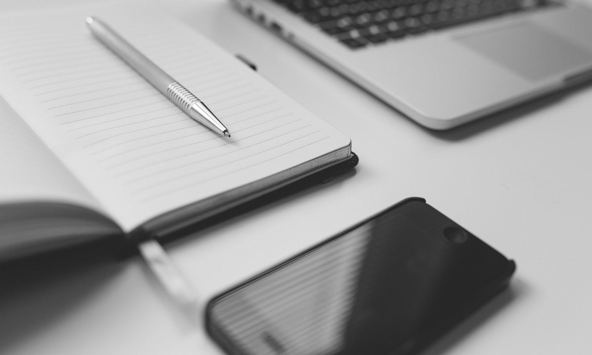 Laptop, Hand und Notizbuch