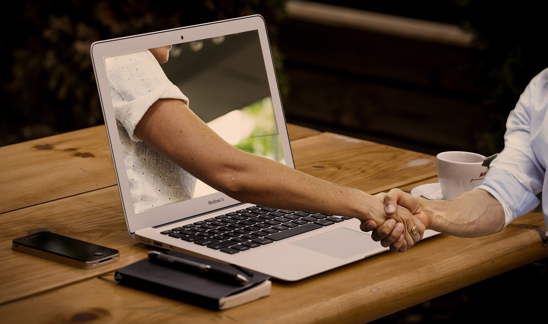 Eine Hand kommt aus einem Laptop und schüttelt eine andere Hand.