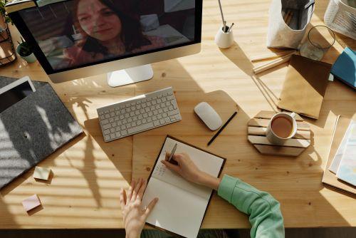 Monitor mit Videokonfernt; auf dem Tisch schreibt eine Person ins Notizbuch, weitere Büromaterialien und eine Kaffeetasse.