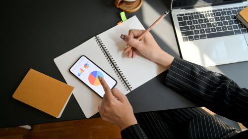 Eine Hand schreibt in ein Notitzbuch. Auch ein Laptop liegt auf dem Tisch.