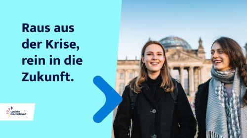 """Links im Bild steht """"Raus aus der Krise, rein in die Zukunft"""" - recht im Bild stehe zwei junge Frauen vor dem Reichstagsgebäude in Berlin."""