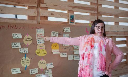 Eine Frau zeigt auf eine Pinnwand voller Post-its.