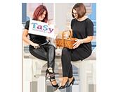 Tanja Helm und Sylvia Musel sitzen auf einem Hocker mit einem Nähkästchen und zerschneiden das TaSy Logo