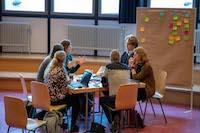 Sechs Lehrkräfte tauschen sich während eines gemeinsamen Meetings miteinander aus.