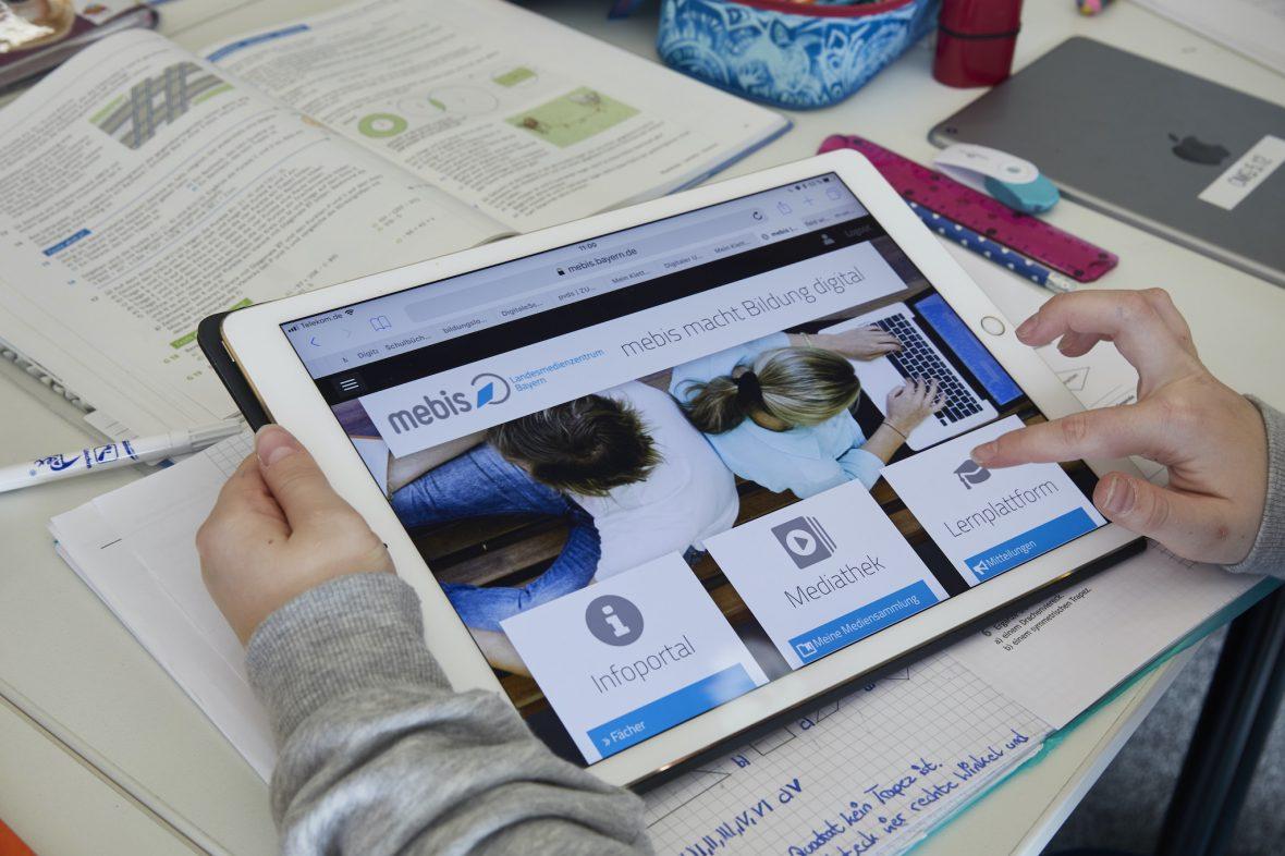 Ein Kind nutzt die Plattform mebis auf einem Tablet.