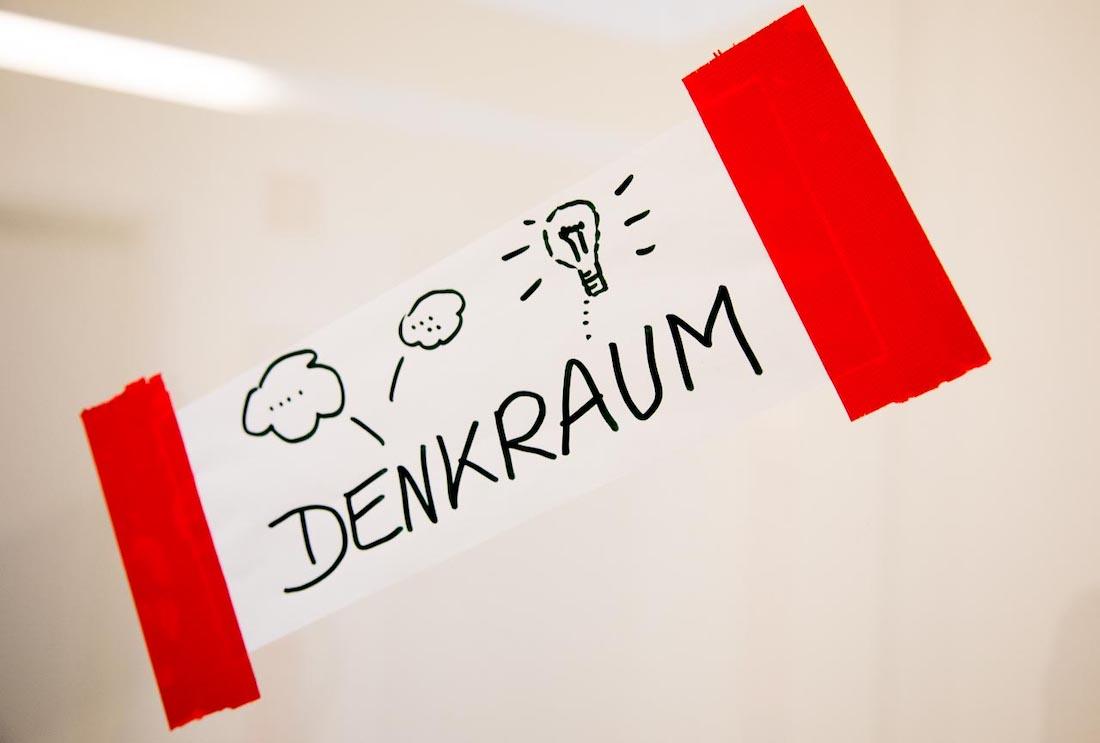 """Ein Post-it mit der Aufschrift """"Denkraum"""" hängt an einer Wand."""