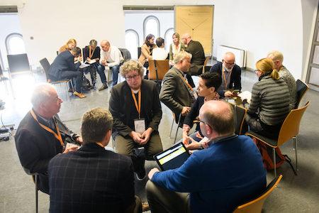 Schulträgern tauschen sich in Gesprächskreisen während einer Veranstaltung aus.