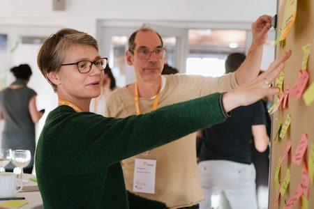 Eine Frau und ein Mann arbeiten kollaborativ an einem Flipchart.